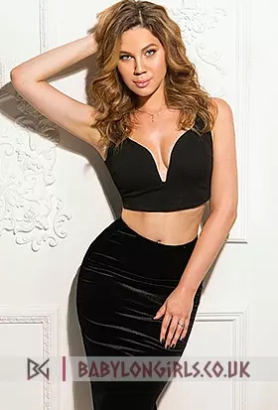 Wild looking blonde escort in black skirt and black top up against the wall